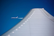 Passenger jet aircraft viewed across plane wing from porthole of another in flight on route to America
