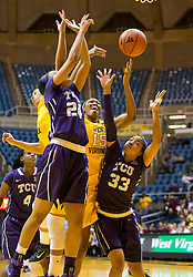 TCU Horned Frogs guard Natalie Ventress (24) and TCU Horned Frogs guard Donielle Breaux (33) try to out rebound West Virginia Mountaineers center Lanay Montgomery (15) at the WVU Coliseum.