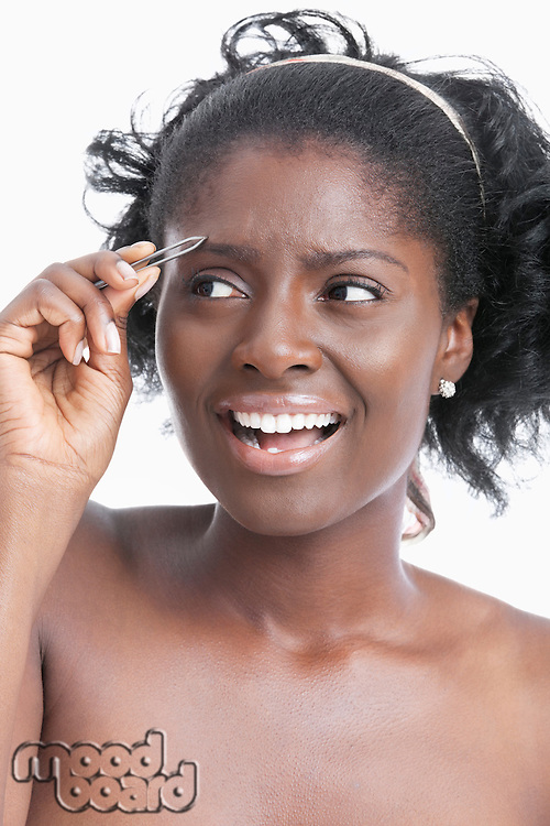 African American young woman tweezing her eyebrows over white background