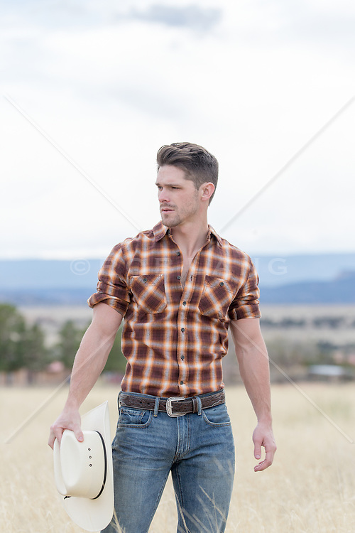 rugged cowboy holding his hat on a ranch