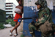 A US soldier takes position to secure a neighborhood from Panamanian army troops during the US invasion of Panama, December 1989.