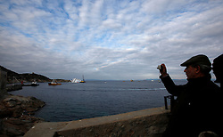 A man takes a photo of the Costa Concordia cruise ship off the west coast of Italy, at Giglio island January 26, 2012. Italy's Civil Protection Agency expects to start extracting fuel from the capsized cruise ship by Saturday or earlier.<br /> REUTERS/Darrin Zammit Lupi (ITALY)