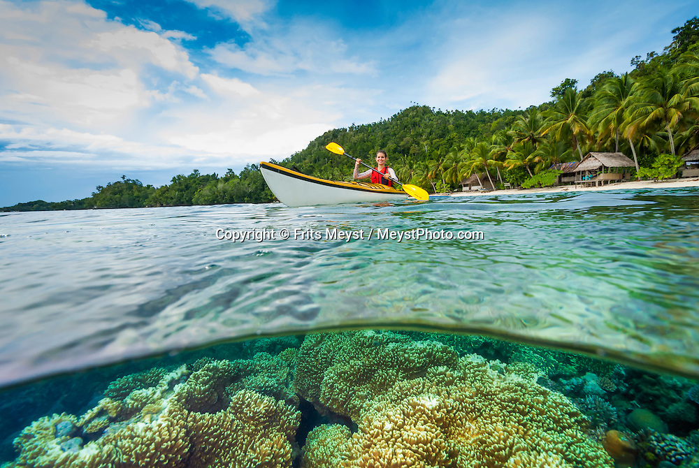 Raja Ampat, West Papua, Indonesia, December 2016. Kayakers over the house reef of Yenanas Paradise Home Stay on the island of Gam. Thousands of small islands fringed by coral reefs and blue water mangroves litter the Raja Ampat archipelago. The turquoise and blue waters are teeming with marine life that forms the livelihood for the local Papuan population. Kayak4conservation is the Raja Ampat Research & Conservation Centre (RARCC) project that supports the locals to develop a community based, sustainable tourism project, inviting visitors to explore their islands by sea kayak with a local guide and experience the culture by staying amongst the local people in traditional style homestays. Photo by Frits Meyst / MeystPhoto.com