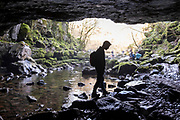 Silhouette of man waling across the river bed rocks at the entrance of Porth-yr-ogof Cave near the village of Ystradfellte, Brecon Beacons National Park, Wales, Powys, United Kingdom. The Afon Mellte River flows into the cave.  (photo by Andrew Aitchison / In pictures via Getty Images)