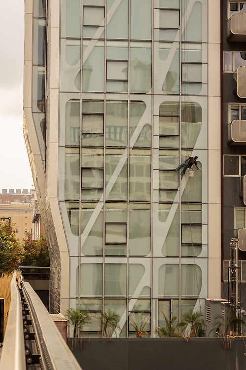 window cleaner hanging on scaffoling at a high rise building,