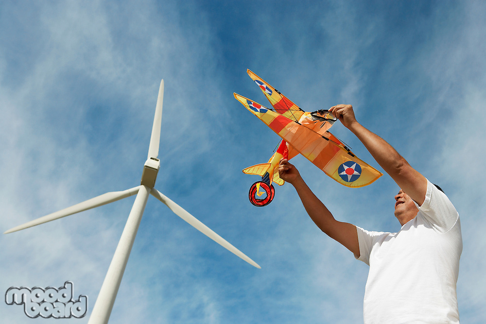 Man holding airplane kite at wind farm