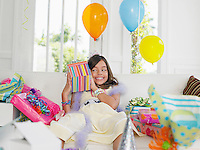 Young girl (7-9) opening birthday presents