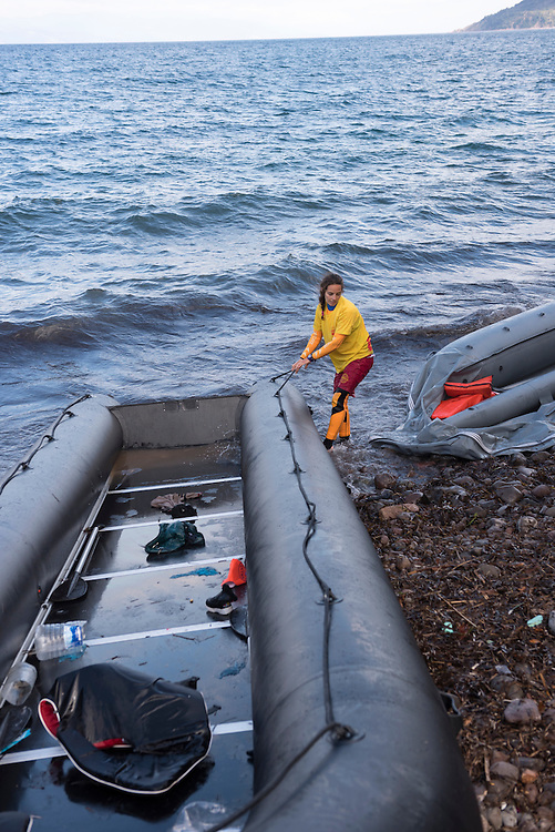 A young female lifeguard volunteering her time to assist migrants arriving from Turkey pulls an inflatable boat to the shore after its passengers disembarked on the north coast of Lesbos, Greece.