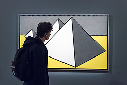 "© Licensed to London News Pictures. 01/10/2018. LONDON, UK. A visitor views ""Pyramids"", 1968, by Roy Lichtenstein (Est. GBP2 - 3m). Preview of artworks in Sotheby's Frieze sales at Sotheby's New Bond Street.  The auction will take place 5 October during Frieze and Frieze Masters – the world's most vibrant Contemporary and Modern art fairs.  Photo credit: Stephen Chung/LNP"