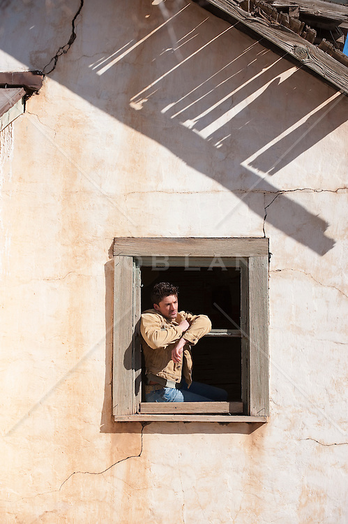 man leaning out of a window in a broken down house in New Mexico