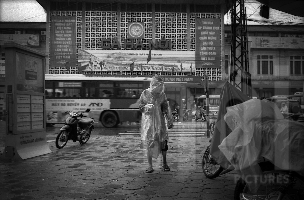 A XE Om, (moto-taxi) is wearing a rain coat in front of the Train Station (Ga Ha Noi).The four November 2008, Hanoi, in Vietnam has been hit by its worst floods in 35 years.  Between Friday and Monday, more than 60 centimeters of rain paralyzed the city, causing massive damage and some twenty deaths. LÍ Duan.Hai Ba Trung