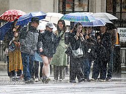 © Licensed to London News Pictures. 26/09/2019. London, UK. Members of the public shelter from heavy rain underneath umbrellas in Parliament Square, Westminster, London. The UK has been deluged with rain causing flash floods in parts. Photo credit: Peter Macdiarmid/LNP