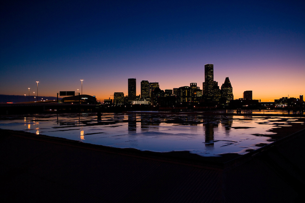Silhouette of the Houston, Texas skyline reflected on a rooftop rain puddle after a storm.