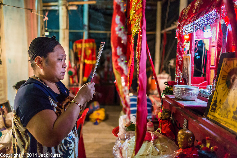 """25 JANUARY 2014 - BANG LUANG, NAKHON PATHOM, THAILAND: A performer with the Sing Tong Teochew opera troupe prays at a Chinese alter backstage before a show in a Chinese shrine in the town of Bang Luang, Nakhon Pathom, Thailand. The Sing Tong Teochew opera troupe has been together for 60 years and travels through central Thailand and Bangkok performing for mostly ethnic Chinese audiences. Chinese opera was once very popular in Thailand, where it is called """"Ngiew."""" It is usually performed in the Teochew language. Millions of Chinese emigrated to Thailand (then Siam) in the 18th and 19th centuries and brought their cultural practices with them. Recently the popularity of ngiew has faded as people turn to performances of opera on DVD or movies. There are still as many 30 Chinese opera troupes left in Bangkok and its environs. They are especially busy during Chinese New Year when travel from Chinese temple to Chinese temple performing on stages they put up in streets near the temple, sometimes sleeping on hammocks they sling under their stage.     PHOTO BY JACK KURTZ"""