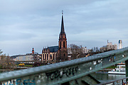 "Germany banned gatherings of more than 2 people called ""social distancing"" because of the coronavirus. The ""Dreikönigskirche"" seen from the ""Eiserner Steg"" (English:Iron footbridge) a footbridge spanning the river Main in the city of Frankfurt, Germany."
