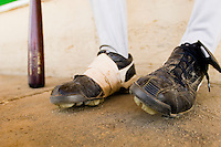 Baseball player sitting close-up of baseball shoes (low section)