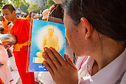 20 OCTOBER 2012 - BANGKOK, THAILAND:  A woman holds a Buddhist prayer card and bows her head in prayer and respect as Buddhist monks pass her at a special alms giving ceremony in Bangkok. More than 2,600 Buddhist Monks from across Bangkok and thousands of devout Thai Buddhists attended the mass alms giving ceremony in Benjasiri Park in Bangkok Saturday morning. The ceremony was to raise food and cash donations for Buddhist temples in Thailand's violence plagued southern provinces. Because of an ongoing long running insurgency by Muslim separatists many Buddhist monks in Pattani, Narathiwat and Yala, Thailand's three Muslim majority provinces, can't leave their temples without military escorts. Monks have been targeted by Muslim extremists because, in the view of the extremists, they represent the Thai state.       PHOTO BY JACK KURTZ