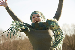 Close up of a woman jumping mid air with arms over head