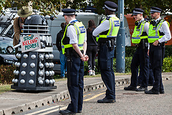 London, UK. 7 September, 2019. Metropolitan Police officers observe a Dalek bearing a sign reading 'Stop Killing People' on the sixth day of Stop The Arms Fair protests outside ExCel London against DSEI, the world's largest arms fair. The sixth day of protests was billed as a Festival of Resistance and included performances, entertainment for children and workshops as well as activities intended to disrupt deliveries to ExCel London for the arms fair.