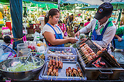 09 OCTOBER 2012 - BANGKOK, THAILAND:  A street food vendor sells a grilled sausage in front of the Bangkok Flower Market. The Bangkok Flower Market (Pak Klong Talad) is the biggest wholesale and retail fresh flower market in Bangkok. It is also one of the largest fresh fruit and produce markets in the city. The market is located in the old part of the city, south of Wat Po (Temple of the Reclining Buddha) and the Grand Palace.    PHOTO BY JACK KURTZ