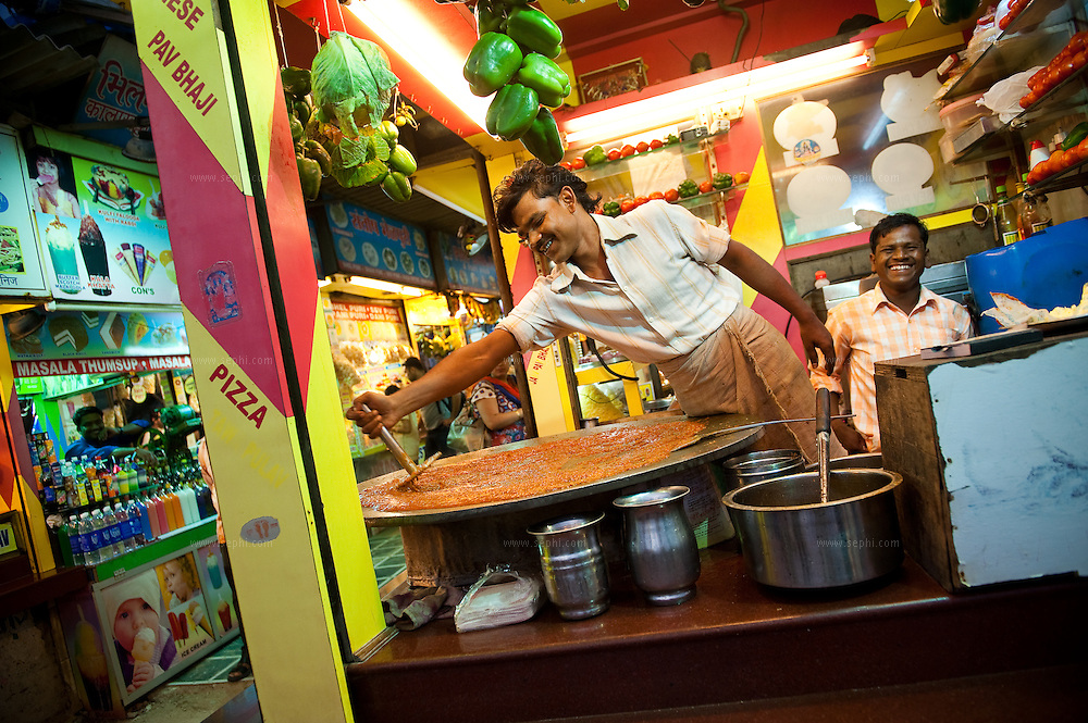 A vendor is making Pao Bhaji, a famous street food dish, at a food stall on Juhu Chowpati beach. Mumbai, August 2009