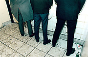 Waist down view of three men using urinals.