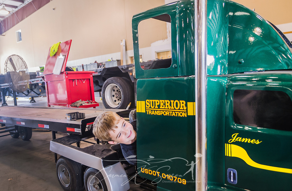 Six-year-old James Barber looks around the side of his custom-built Mack go-cart at Superior Transportation, Sept. 30, 2015, in North Charleston, South Carolina. Barber started the company in 1998. James, 6, is already showing a big interest in the company and its Mack trucks, and Barber says he hopes he will follow in his footsteps and carry on the family legacy.  (Photo by Carmen K. Sisson/Cloudybright)