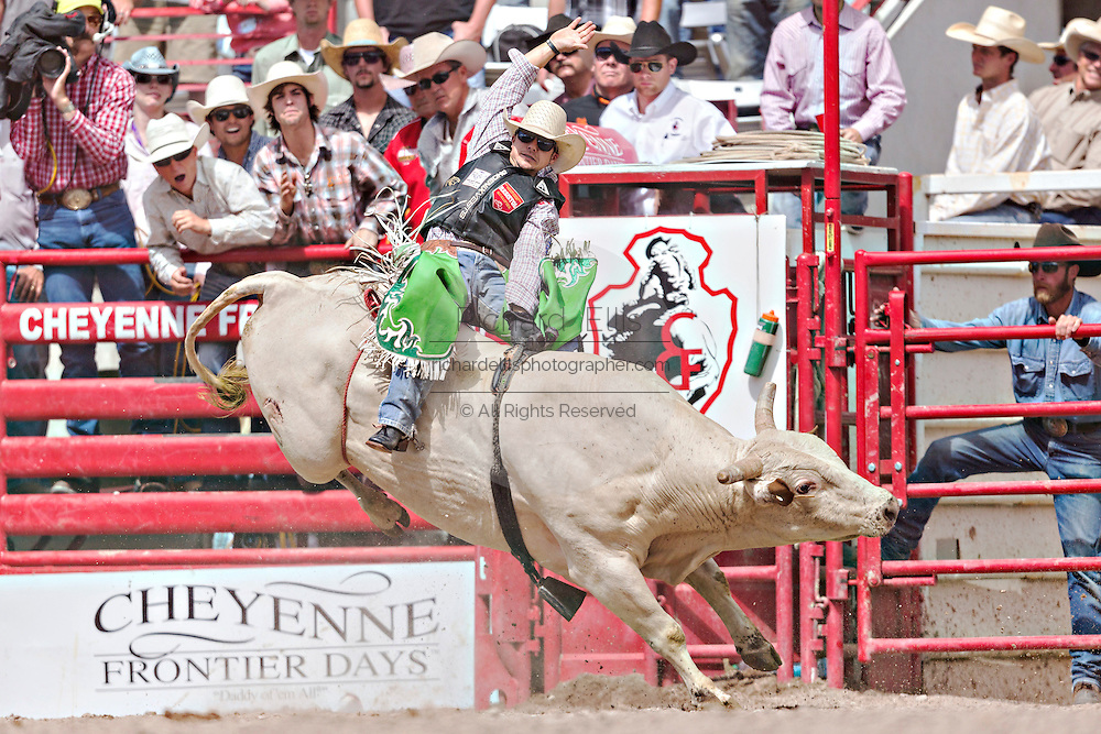 Bull rider Aaron Pass hangs on during the Bull Riding finals at the Cheyenne Frontier Days rodeo in Frontier Park Arena July 26, 2015 in Cheyenne, Wyoming. Pass went on to win the Bull Riding Championship.