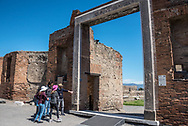 POMPEII, ITALY - APRIL 7, 2018: The Rivoli family studies the marble frieze decorating the grand Portico of Concordia Augusta, also known as the Building of Eumachia. It's now believed that this decorative door frame found in the ruins was placed here in error and instead belonged to the neighboring Temple of Genius Augusti.
