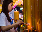 27 SEPTEMBER 2014 - BANGKOK, THAILAND:  A woman lights incense during the celebration of the Vegetarian Festival at the Chow Su Kong Shrine in Talat Noi, a Chinese enclave in Bangkok. The Vegetarian Festival is celebrated throughout Thailand. It is the Thai version of the The Nine Emperor Gods Festival, a nine-day Taoist celebration beginning on the eve of 9th lunar month of the Chinese calendar. During a period of nine days, those who are participating in the festival dress all in white and abstain from eating meat, poultry, seafood, and dairy products. Vendors and proprietors of restaurants indicate that vegetarian food is for sale by putting a yellow flag out with Thai characters for meatless written on it in red.   PHOTO BY JACK KURTZ