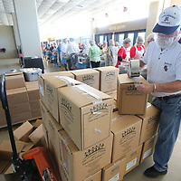 Thomas Wells | BUY at PHOTOS.DJOURNAL.COM<br /> Ed Calbert seals up boxes full of food packaged by volunteers during Friday's food packing at the BancorpSouth Arena.