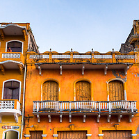 One man sits on the top balcony of an old colonial building in the old town district of Cartegena, Colombia.
