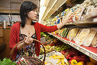 Young woman choosing mushroom package in market