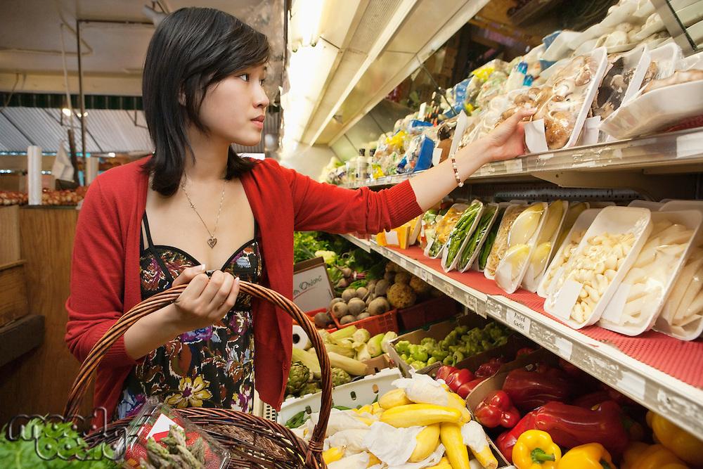 Young woman choosing mushroom package in market