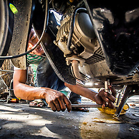 Jan 3, 2013 - A repair shop employee changes the oil on a moped in the Cambodian capital city of Phnom Penh.<br /> <br /> Story Summary: Amidst the feverish pace of Phnom Penh&rsquo; city streets, a workhorse of transportation for people and goods emerges: Bicycles, motorcycles, scooters, Mopeds, motodups and Tuk Tuks roam in place of cars and trucks. Almost 90 percent of the vehicles roaming the Cambodian capital of almost 2.3 million people choose these for getting about. Congestion and environment both benefit from the small size and small engines. Business is booming in the movement of goods and and another one million annual tourists in Cambodia&rsquo;s moto culture.