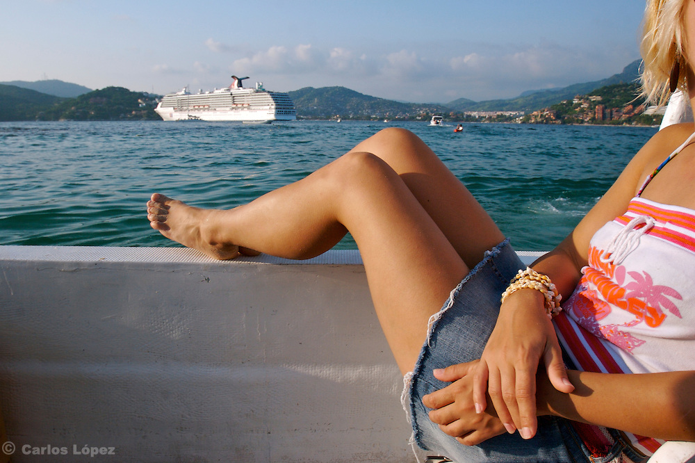 A pair of legs in front  of a nice view of a cruise ship.