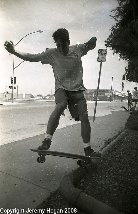 A skateboarder grinds on a curb in Porterville, California during an illegal street skating session.