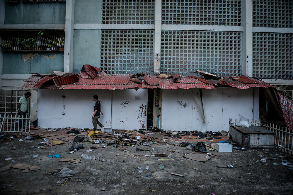 """CARACAS, VENEZUELA - APRIL 21, 2017:  Jian Feng Wu inspects the damage to Vicruz supermarket, that was one of over a dozen stores looted late last night in El Valle, a working class neighborhood in Caracas. """"They took everything,"""" he said. The streets of Caracas erupted into a night of riots, looting and clashes with National Guardsmen as anger from two days of pro-democracy protests spilled into unrest in working class neighborhoods and slums. Shots rang out throughout the night in El Valle, a neighborhood of mixed loyalties, as armored vehicles struggled to contain crowds of looters. At one point during the night, clashes became so heavy that a nearby children's hospital was evacuated after the ward filled with tear gas. The government said they were responding to an attack on the hospital by opposition protestors.  PHOTO: Meridith Kohut"""