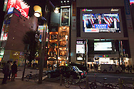 Tokyo, Japan - November 9, 2016: Pedestrians in front of Tokyo's Shinjuku Station watch the evening news explaining Donald Trump's victory in the the US presidential election which came as a shock to most Japanese. Financial markets around the world went into a tailspin as did currency exchange rates. In Japan the US dollar dropped rapidly from around 105 yen to a dollar to 101 yen by midday. The Nikkei 225 index also nose-dived by 5.36 ending down 919.84 points from the previous at 16,251.54. (Torin Boyd/Polaris).