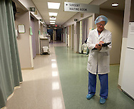 Dr. John Phillips works on a form as he walks down the surgery floor at Great River Medical Center in West Burlington, Iowa on Monday December 22, 2008.