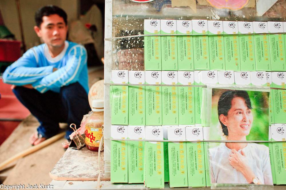Oct. 6, 2009 -- SAMUT SAKHON, THAILAND: A Burmese man sits behind a stall that sells beetle nut and Chinese ointments with a photo of jailed Burmese opposition leader Aung San Suu Kyi on the front of the display case in Samut Sakhon, Thailand, Oct. 6. Some Thais refer to the area as Little Burma because of the large number of Burmese migrant workers who are employed in the town's fishing industry. The Thai fishing industry is heavily reliant on Burmese and Cambodian migrants. Burmese migrants crew many of the fishing boats that sail out of Samut Sakhon and staff many of the fish processing plants in Samut Sakhon, about 45 miles south of Bangkok. Migrants pay as much $700 (US) each to be smuggled from the Burmese border to Samut Sakhon for jobs that pay less than $5.00 (US) per day.   Photo by Jack Kurtz / ZUMA Press