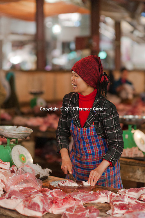 A woman sells pork from her stall in the markets in Sapa, Vietnam.