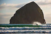 Lone surfer in front of Haystack rock at Cape Kiwanda in pacific city, oregon.
