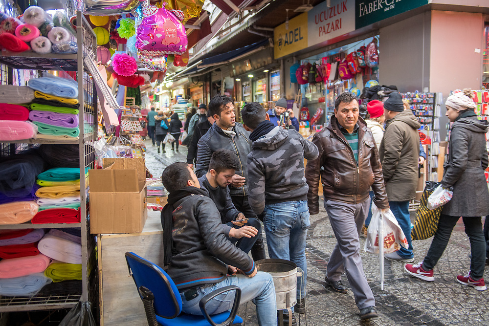 Group of men gather together to share information on their cellphones in front of storefront, Istanbul, Turkey