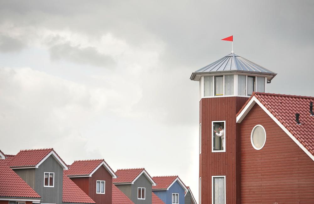 A painter applying the finishing touches to a house in the Reitdiep Haven, a new residential area in the city of Groningen // Een schilder aan het werk in Reitdiep Haven, een nieuwe woonwijk in Groningen.