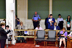 Police officer checks a mobile phone during public testimony by community members and activists on controversial social media posts by officers of the Philadelphia Police Department (PPD) that were unearthed by the Plain View Project, during a council hearing on June 20, 2019 at City Hall in Philadelphia, PA.