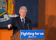 Elmont, New York, USA. April 5, 2016. Former President Bill Clinton, with his hands in wide open gesture, is the headline speaker as he campaigns at an Organizing Event rally in Elmont, Long Island, on behalf of his wife, Hillary Clinton, the leading Democratic presidential candidate, and former Secretary of State and U.S. Senator for New York. Podium has 'Fighting for us' slogan on sign. The New York Democratic Primary takes place April 19th.