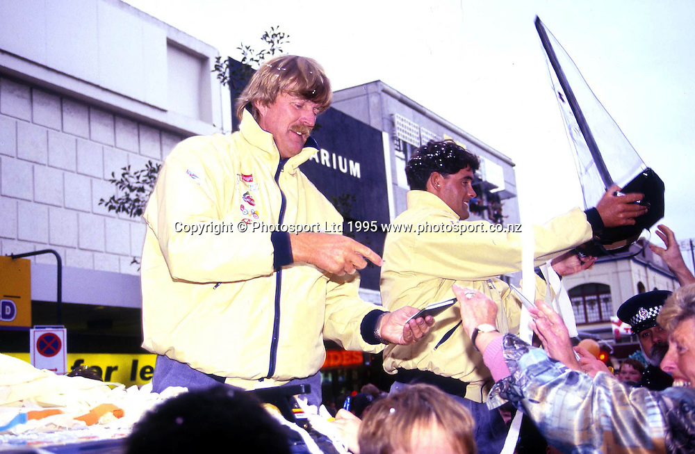 Sir Peter Blake and Russel Coutts sign their autographs for fans at the ticker tape parade welcoming them and the America's cup home at Queen Street, Auckland, 1995. Photo: PHOTOSPORT<br />