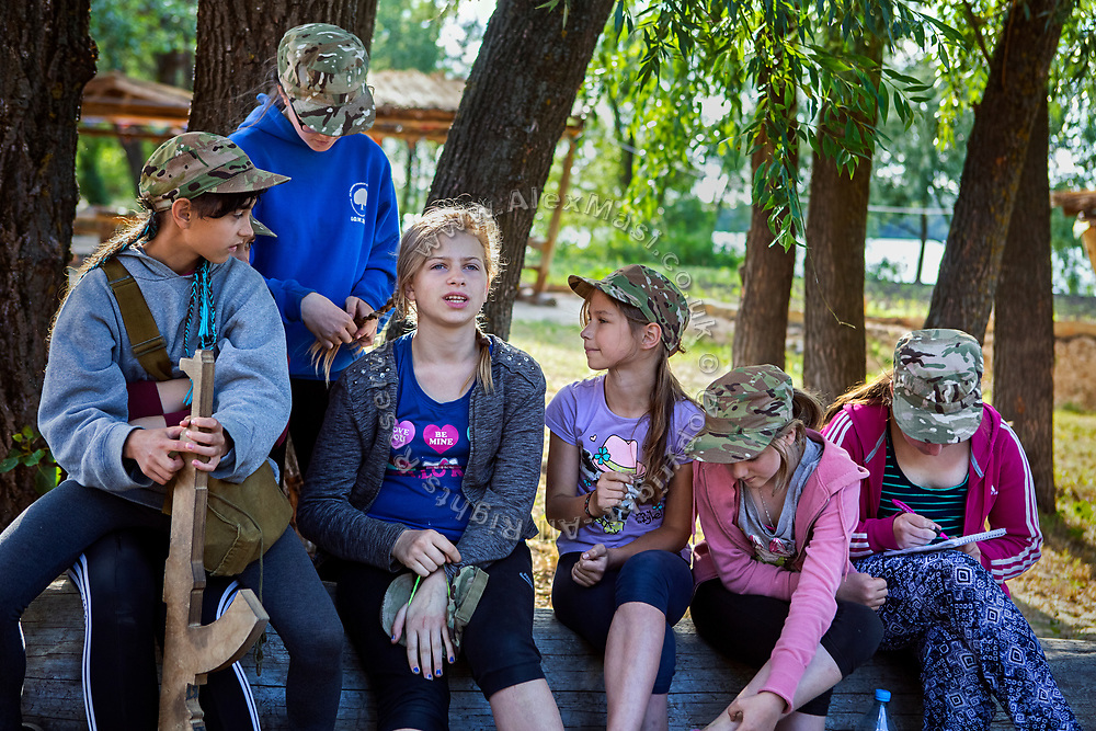 Girls participating to the ultra-nationalistic Azovets children's camp are sitting together, chatting and taking care of each other's hair, after a long day of  training on the banks of the Dnieper river, in Kiev, Ukraine's capital.