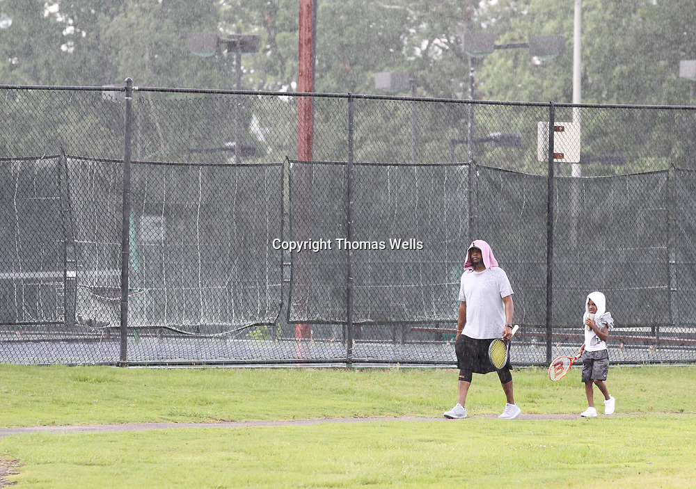 Christopher Sampson, left, and his son, Tristen, 7, use their towelsto try and stay dry after a Tuesday morning rain shower forced them off the tennis courts at Rob Leake Park.